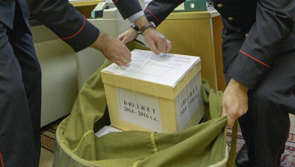 Сотрудники Государственной фельдъегерской службы (ГФС) упаковывают коробки с документами и материалами проекта федерального бюджета на период 2014-й и 2015-2016 годы