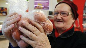 Покупательница выбирает куриные яйца в продуктовом магазине