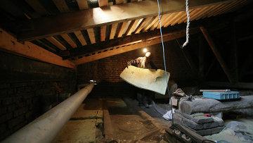 Рабочий утепляет чердак многоэтажного дома. Архивное фото