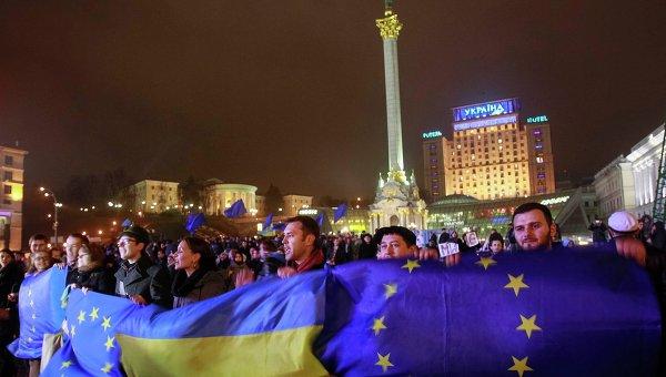 Протестующие держат украинские флаги и флаги Евросоюза во время митинга в поддержку евроинтеграции, Киев