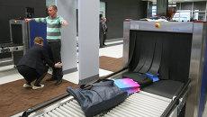 Сотрудница аэропорта досматривает пассажира. Архивное фото