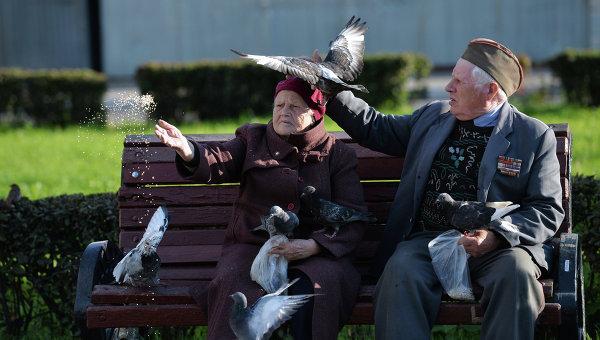 Пожилые люди кормят голубей, архивное фото