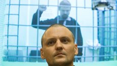 Оппозиционеры Сергей Удальцов и Леонид Развозжаев (на экране) во время рассмотрения апелляции их защиты. Фото с места события