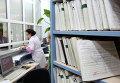 Медицинский работник выдает медицинскую карту пациенту в регистратуре районной поликлиники